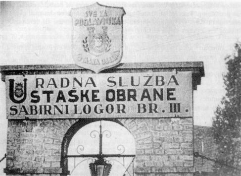 Photo d'une porte en pierre avec une voute. Une pancarte avec peinte en gosses lettres l'inscription : RADNA SLUZBA, STASKE OBRANE, SABIRNI LOGOR BR. III