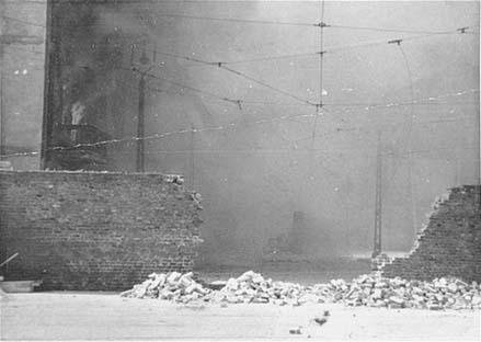 Photo du mur du ghetto dans lequel il y a une brèche. On ne distingue rien de l'intérieur du ghetto à cause de la fumée.