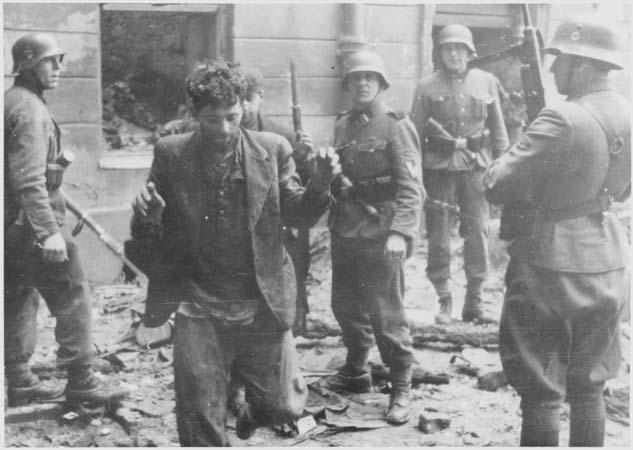 Photo dans une rue pleine de gravats. Deux hommes en civil, hirsutes, lèvent les bras. Ils sont entourés par quatre soldats allemands armés, avec casques, qui les regardent.
