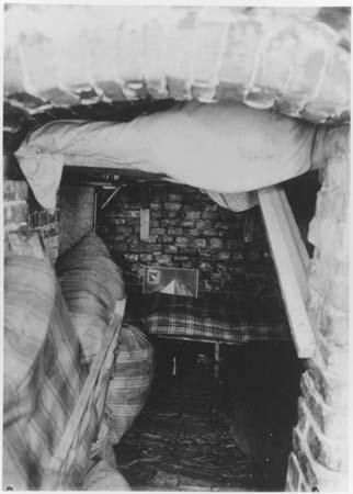 Photo prise depuis l'entrée étroite d'une cave. Au fond, une couchette recouverte d'une couverture à carreaux.