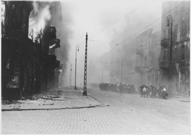 Photo d'une rue du ghetto. A gauche un immeuble brûle, des flammes sortent du premier étage. Sur la droite de la rue, assez loin, des groupes de civils marchent dans la fumée en s'éloignant de l'objectif.