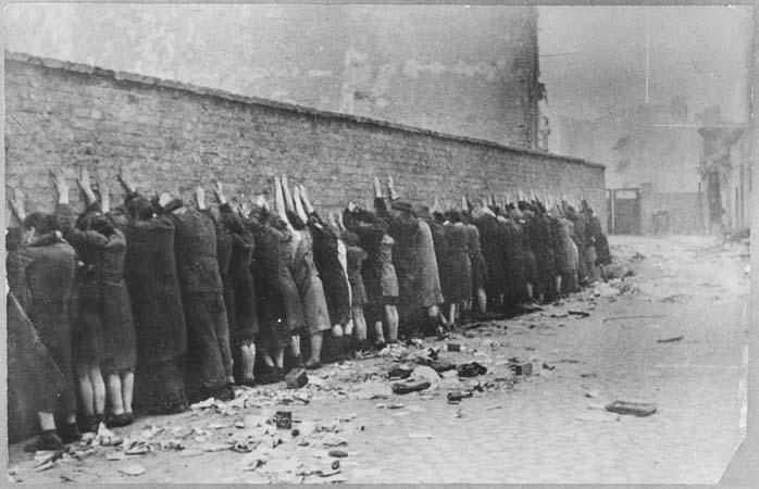 Photo du mur du ghetto : une trentaine de personnes y son collés, tournant le dos, les mains en l'air appuyées sur le mur. Au sol des gravats. On ne voit pas de soldats.