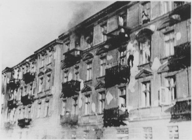 Photo d'une façade d'immeuble de 4 étages. Un homme est e train de tomber, dans le vide, entre le 4ème et le 3ème étage.