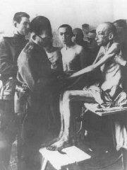 Médecin militaire soviétique examinant un déporté, après la libération du camp.