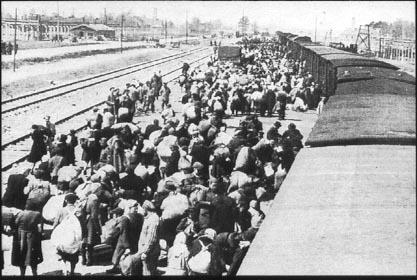 Photo : sur la droite un long train qui forme une courbe, on n'en voit que les toits. A gauche, deux voies ferrées vides. Au milieu, sur le quai, le train se vide : des hommes et des femmes dont on ne voit que les dos, portant parfois des ballots d'affaires. Il marchent en s'éloignant de nous. Au fond, des cheminées à la fumée très noire.